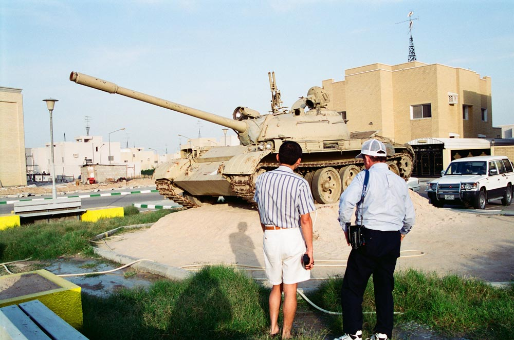 Al-Qurain House Exterior in 1993  Fathers of two American soldiers killed during the Gulf War look at one of the Iraqi tanks that fired on the house. The tank's gun still points at the house. Nicolas Fajardo is on the right. His son, Army Captain Mario Fajardo of the 82nd Airborne Division, and six of his men were killed on Liberation Day while clearing a land mine. (See also Overview pages 35-36.)