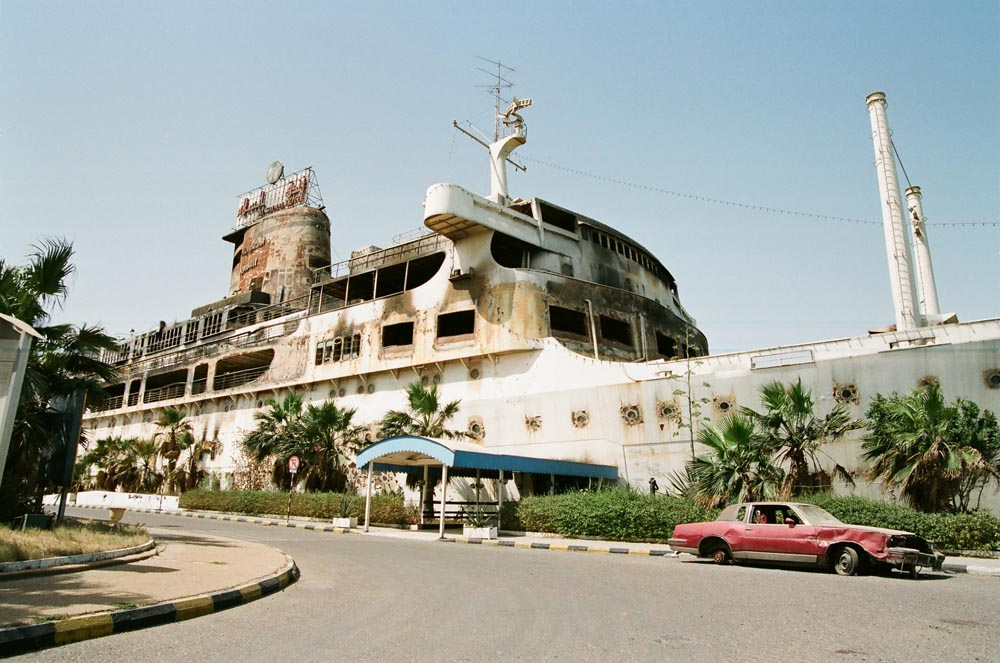 Ramada Al-Salam Hotel Exterior  Iraqi firebombing totally destroyed the floating hotel. A car vandalized by the Iraqis is parked next to the vessel.