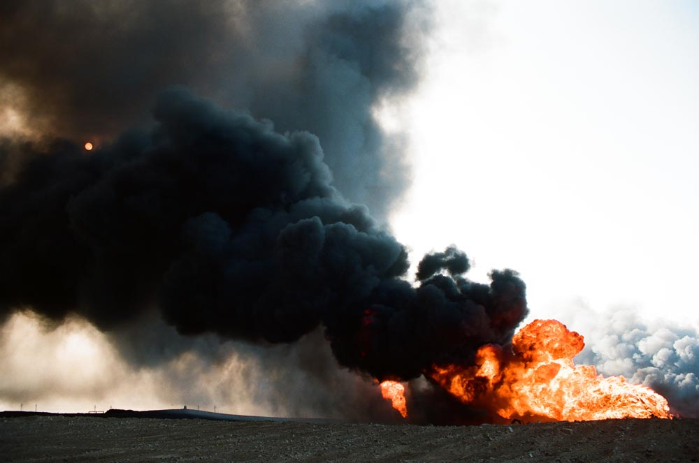 Oil Well Fires and Black Smoke  Two fires and smoke plumes. The sun is visible behind the black plume.