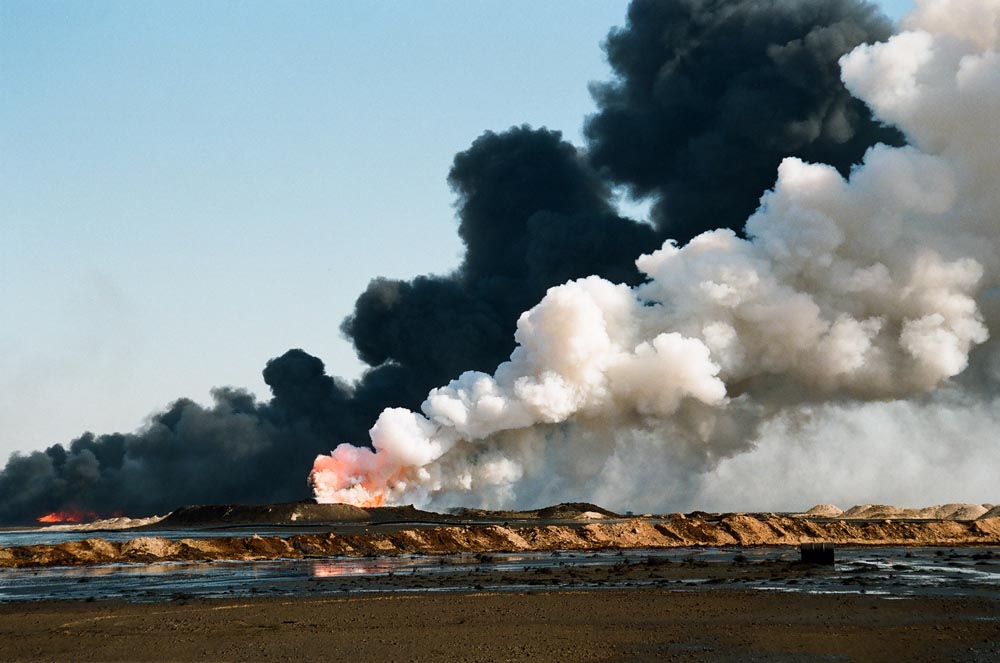 Oil Well Fire, Oil Lake, and Smoke  Black and white smoke polluting the air while an oil spill spreads across the land